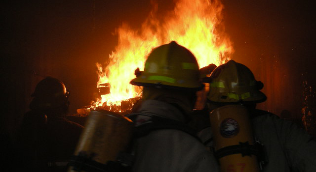 Three firefighters approaching large fire